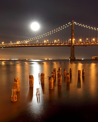Bay Bridge and Full Moon (Rob Kroenert) Tags: sanfrancisco california ca bridge usa moon night bay san francisco long exposure full fullmoon baybridge embarcadero pilings