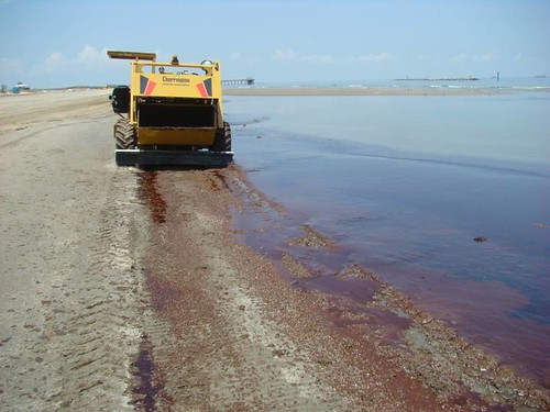 An oil skimming vehicle in action on a polluted beach