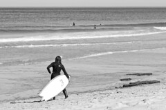 Studying the Break (brucetopher) Tags: surfer girl wetsuit surfboard water beach break boys girls surfing wave waves board standing looking watching woman man people watersports sports summer coldwater sea ocean atlantic coast coastline holiday vacation black white blackandwhite bw blackwhite monochrome contrast tone tones