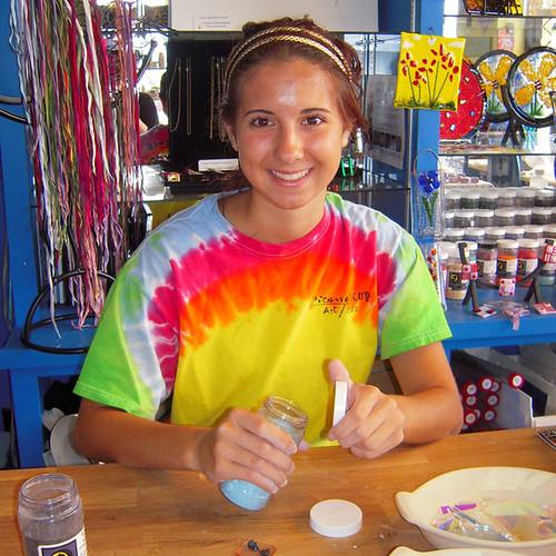 fused glass pendant workshop instructor holding a bottle of frit.