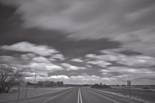 black 'n white photograph of a two-lane highway in new mexico, and enormous clouds and sky
