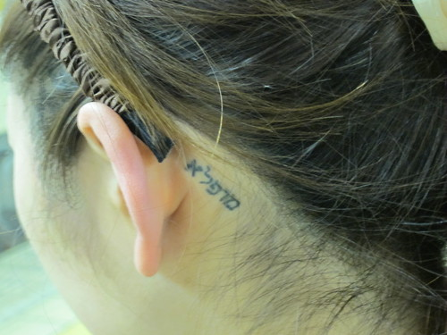 I noticed a Tattoo in Hebrew behind her ear. Tattoos are not common in