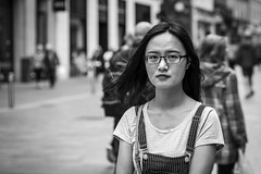 The Bib and Brace (Leanne Boulton) Tags: urban street candid portrait portraiture streetphotography candidstreetphotography candidportrait eyecontact candideyecontact streetlife woman female girl face facial expression eyes look emotion feeling mood dungarees braces glasses wind breeze hair tone texture detail depthoffield bokeh naturallight outdoor light shade shadow city scene human life living humanity society culture people canon canon5d 5dmarkiii 70mm character ef2470mmf28liiusm black white blackwhite bw mono blackandwhite monochrome glasgow scotland uk