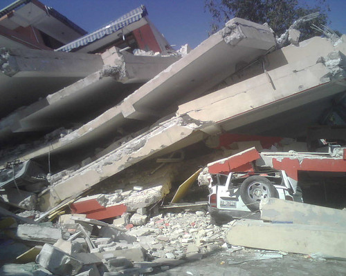 A leveled multi-story structure illustrates the earthquake's force.