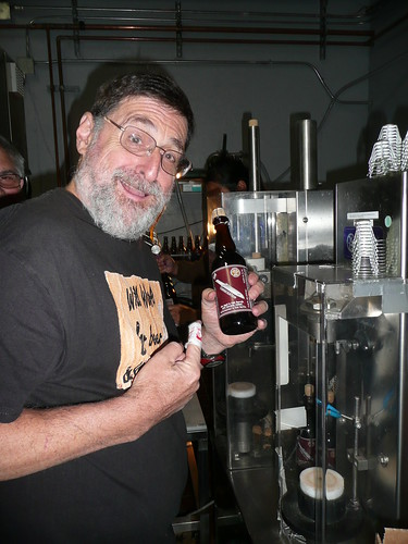 Pete Slosberg, helping out for the day, shows off a finished bottle