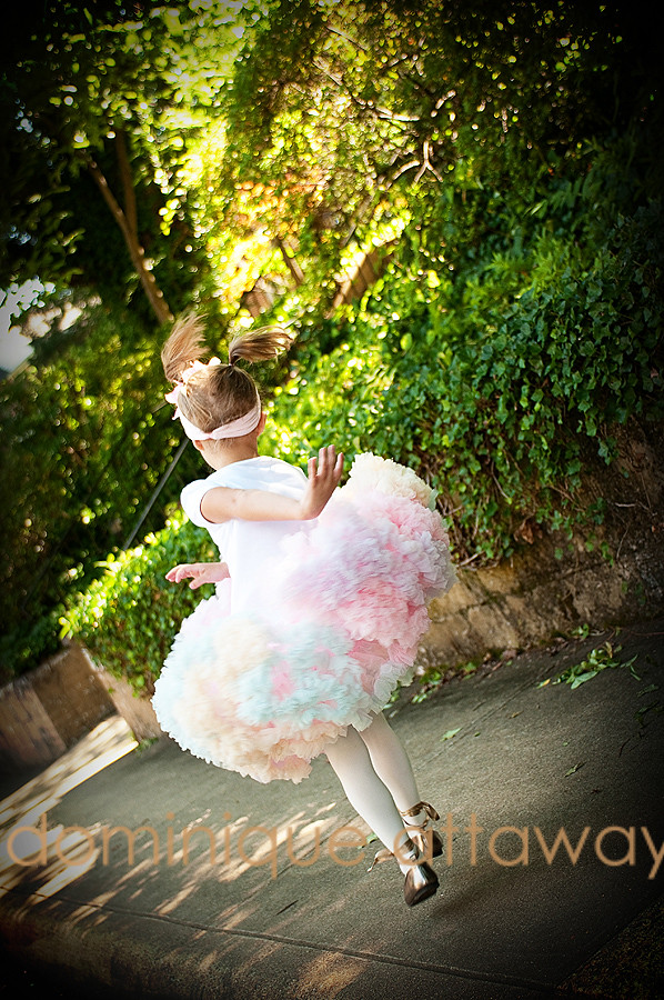 little girl in tutu skipping in the street