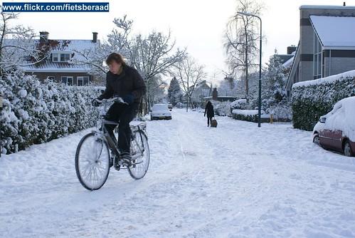 Fietser in woonstraat met dik pak sneeuw