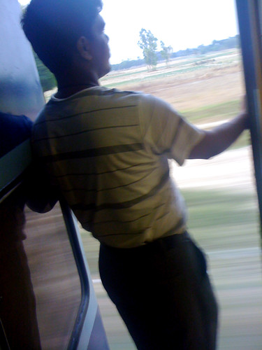 インドの電車から外を眺める人