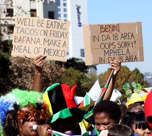 Los hinchas de Sudáfrica (Bafana) con letreros sobre comer tacos de mexicanos