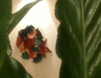 Arty shot of quilted autumn leaves wall hanging, as seen through calathea leaves