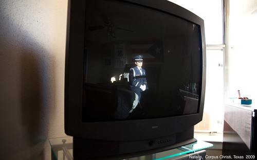 A photograph of a blank television screen, a woman's reflection cast convexly in its black screen. She sits stoically, in uniform, her cap pulled over her face. You can vaguely make out a Puerto Rican flag hanging behind her.