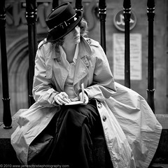 Take Note (Revisited) (Photography JC) Tags: street portrait woman hat lady female pen notebook mac bars iron thought legs artistic diary femme documentary class portraiture pensive chic elegant raincoat graceful railings sophisticated journalism crossed urbane elegance genteel refined sophistication cultivated classsy