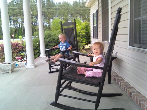 Kids in rocking chairs on the front porch.