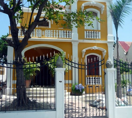 Gold colored house with gate