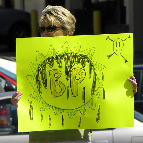 A woman holding a sign at a BP protest