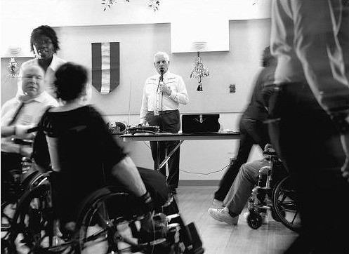 black and white photo of wheelchair users squaredancing, and a caller. There is movement blurring.