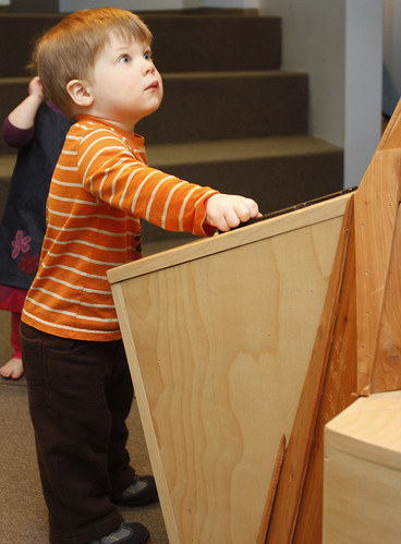 """February 3, 2010 - Bennett Evetti, 2, reacts to the wolf howls that come out of the tree as he moves the levers at the """"Out on a Limb"""" tree exhibit at Holyoke children's museum."""