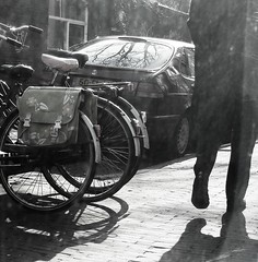 Casting Shadows [Day 61/365] (indigo_jones) Tags: auto shadow blackandwhite bw sunlight man holland reflection window netherlands car walking movement utrecht nederland bikes fietsen raam transporation saddlebag project365 loopen project3652010