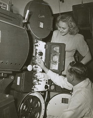 R.J. (Bob) Lucas and unidentified woman looking at a Centrex projector, 1940 - 1949