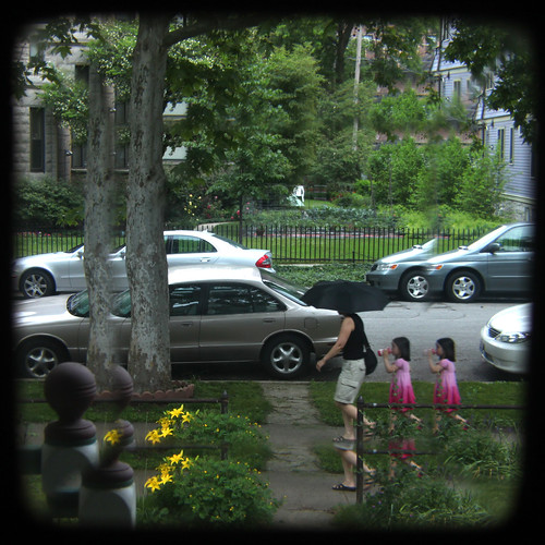 Black umbrella and twin girls in pink