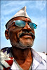 PANDIT (Apratim Saha) Tags: old blue portrait people music cloud sun india man color reflection glass festival painting glasses nikon indian oldman nikond70s sunglass priest dailylife spectacles kolkata 1870mm pilgrim ganga nationalgeographic ganges mela pandit westbengal 1870 saha northindia siliguri gangasagar apratim lifeinindia earthasia gangasagarmela lifeculture apratimsaha