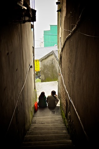 a couple sits at the bottom of a narrow set of stairs