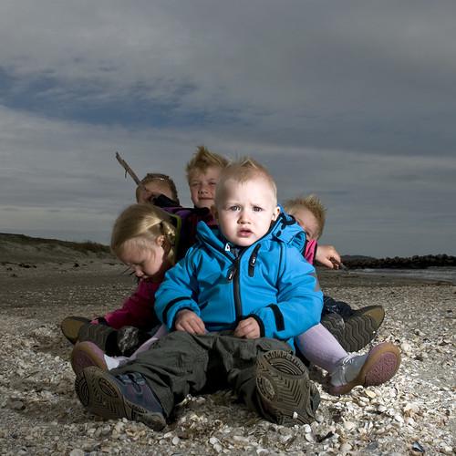 Little man on a beach with friends.