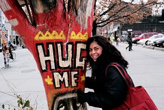 Lavina and the Hug Tree (Georgie_grrl) Tags: toronto ontario cute smile graffiti friend downtown please pentaxk1000 queenstreetwest artpiece lavina hugme hugtree cans2s playingshy rikenon12828mm