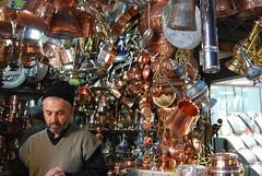 copper merchant. (yumyumbubblegum) Tags: street city orange man black classic hat tin gold iran islam capital decoration plate architect copper jar vest bazaar tehran ornate sell merchant seller prerevolution