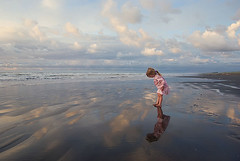 wonder. (child, little girl, and her reflection in the sand. low tide at the beach) (Le Fabuleux Destin d'Amlie) Tags: ocean sunset sea newzealand summer sky holiday reflection beach nature water girl weather childhood kids clouds wonder landscape evening three kid still sand toddler waves quiet peace child play looking pentax ns tide review wideangle explore getty summertime f56 awe curiosity aotearoa pv forme dpc zoomlens 18mm wetsand kapiticoast waitarere 160sec 1645mm exploreflickr k10d 835pm familygetty2010 gettyvacation2010 gettyimagesportraits mfset
