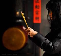 Faith (Yug_and_her) Tags: travel light red woman black macro religious temple sticks nikon drum availablelight candid buddhist smoke burning jacket offering incense 105mm d90 haircoveringface pryaers chinestext