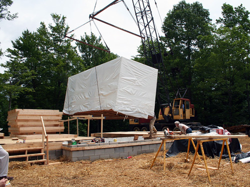 A crane is used to place a pre-fabricated unit consisting of a kitchen, bathroom and utility room onto the foundation of Kristi Wilson's new home.