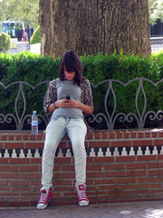 Calling Home (Kombizz) Tags: tree home girl fashion square spain sitting jean candid bricks andalucia espana teen hedge granada mobilephone trunk costadelsol calling waterbottle petit iphone callinghome kombizz