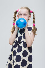 Portrait of Funny Caucasian Blond Girl With Pigtails Posing in Polka Dot Dress Against White. Blowing Up Blue Air Balloon. (DmitryMorgan) Tags: 1 710years adorable airballoon baby beautiful blond blowup caucasian cheerful child childhood daughter dress european expression female fun girl heartformed holding human inflate joy kid little love model mood one pigtails polkadot portrait positive preschooler school schoolgirl small smile smiling straw studio white young