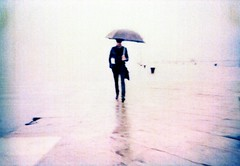 It's a secret (ale2000) Tags: street sea man rain stone umbrella walking geotagged grey seaside xpro mare grigio kodak walk crossprocess candid cosina uomo photowalk pietra pioggia molo trieste cx2 moloaudace passeggiata audace epr ombrella aledigangicom geo:lat=45652114 geo:lon=13766455