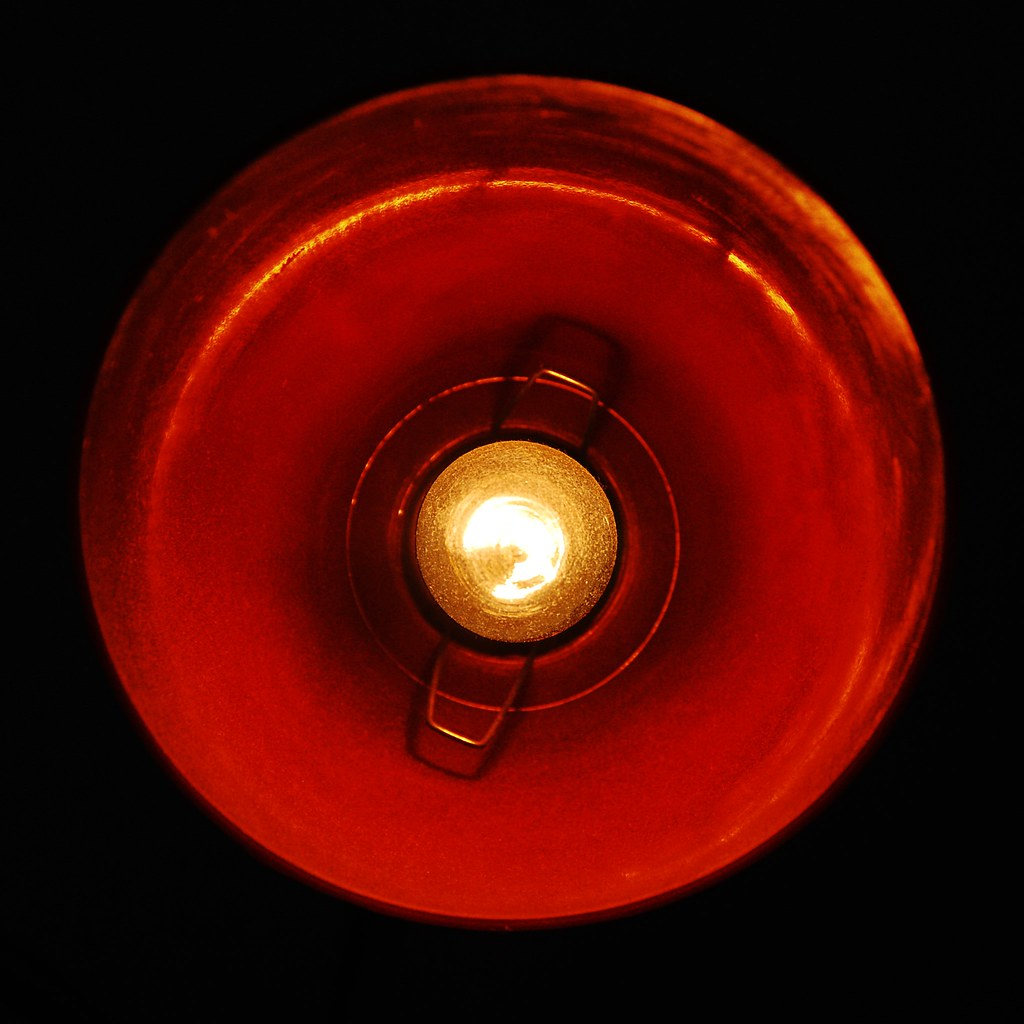 Looking straight down the red reflector of a lamp.