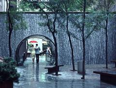 Just Walkin' in the Rain, New York (Rikx) Tags: street plaza people newyork love fountain rain umbrella walking waterfall arch romance together romantic rockefellercentre singingintherain walkinintherain matchpointwinner flickrduelwinner blinkagain bestofblinkwinners