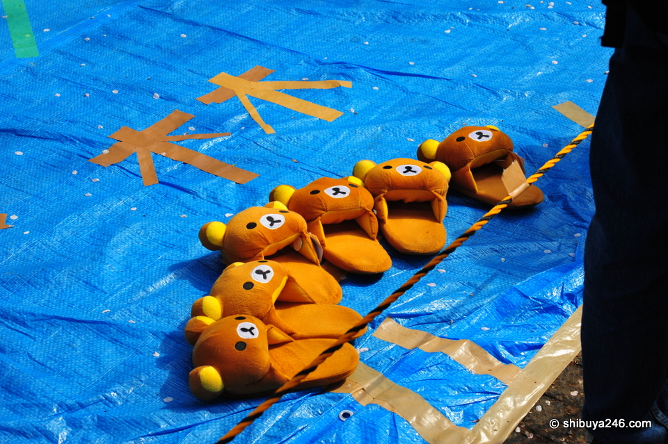 Rilakkuma slippers waiting for their owners to claim the space.