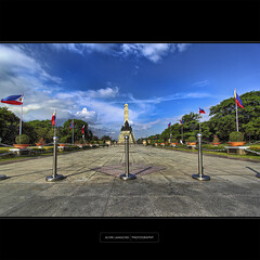 Ode to Patriotism [Luneta - HDR] (alvin lamucho ) Tags: trees monument clouds philippines perspective sunny flags hero manila historical poles hdr rizalpark canon500d lunetapark bagumbayan philippineflags t1i alvinlamucho