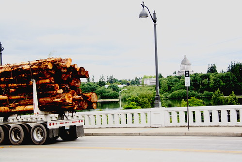 Log Truck Descending 4th Ave Bridge in Olympia Washington with Capitol Lake and Dome