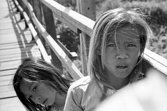 "Two girls on bridge at border - Cambodia (Sailing ""Footprints: Real to Reel"" (Ronn ashore)) Tags: poverty life street blackandwhite film kids portraits children 50mm cambodia faces poor summicron f2 towns needy trixkodak m4leica hc110rangefinderleica 2009dec094014leicam4leicasummicron50mmf2trix800kodakhc11 2009dec094014leicam4leicasummicron50mmf2trix800kodakhc1104m15cambodia iiiborder"
