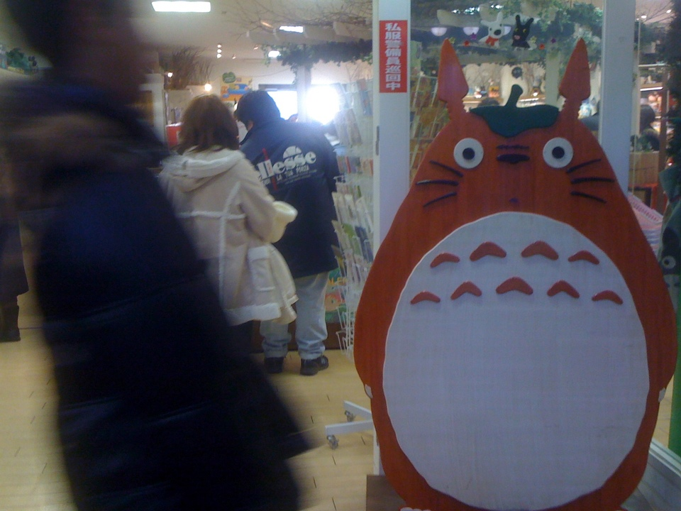 Totoro guarding the entrance to this store. He looks surprised by the guy passing by in black.