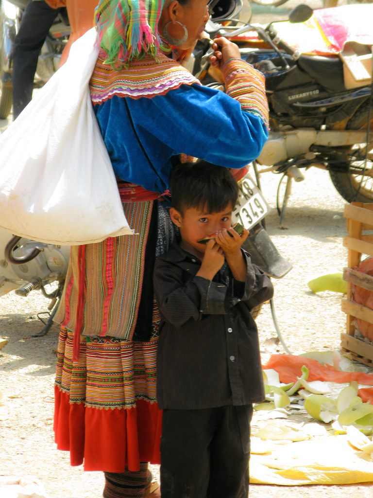Bac Ha Market : A boy and his mother enjoy some Melon while waiting for a bus. Vietnam