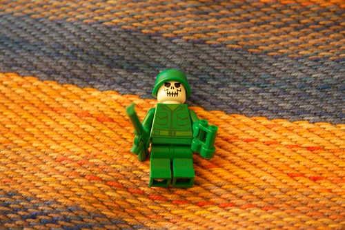 A Lego army man with a skull instead of a head
