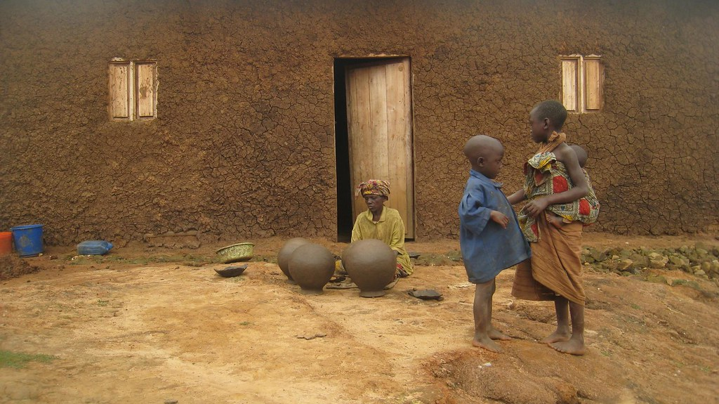 A woman works on several clay pots in front of her home.
