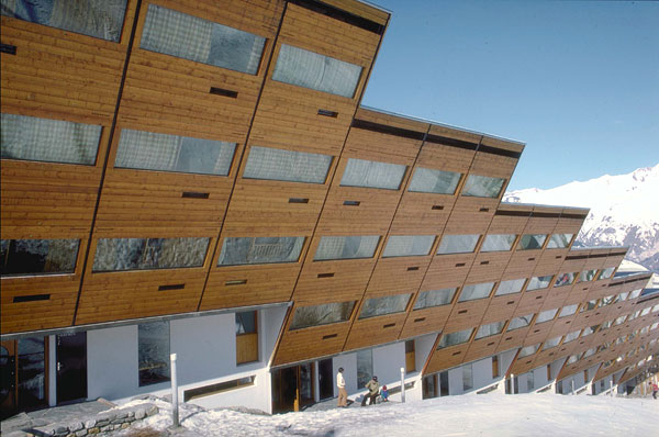 a side of a ski lodge that descrends down a mountain. Its walls are sloped toward the ground, and its roof is a diagonal line.