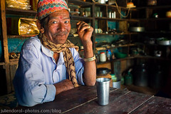 Want a tea? (Julien Dorol) Tags: world travel nepal portrait food man kitchen glass hat smiling scarf table asian restaurant cafe eyecontact asia tea drink interior watch shelf alcohol nepalese ricewine tikka teashop raksi rakshi