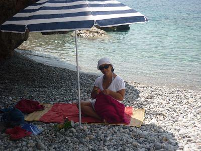 Sofia, brasileira que mora na Grécia, tricota na praia, sob um calor de 40º graus