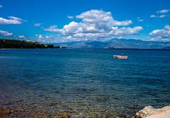 Lone boat (Shawn Blanchard) Tags: greece greek aegean sea water lake blue green rocks white clouds sky boat red island mountains landscape view beautiful beach