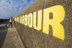 no fishing into harbour (simon.anderson) Tags: portrait sky girl yellow wall clouds concrete person words brighton walkway speech shouting 2010 brightonmarina sigma1020 nikond80 nofishingintoharbour
